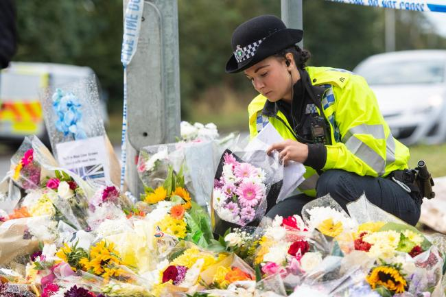A police officer arranges flowers left near the scene in Sulhamstead, Berkshire