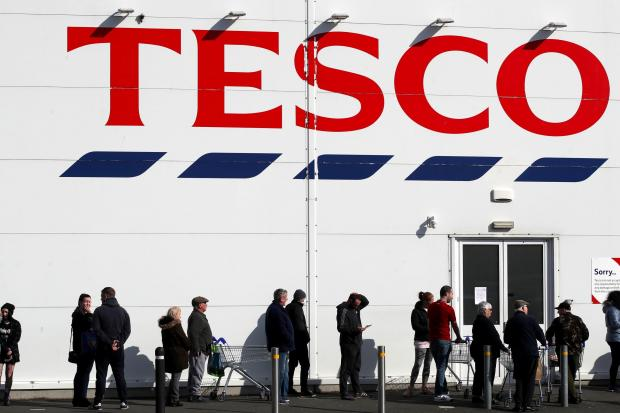 St Helens Star: People queue outside a Tesco Extra store in Madeley, Shropshire