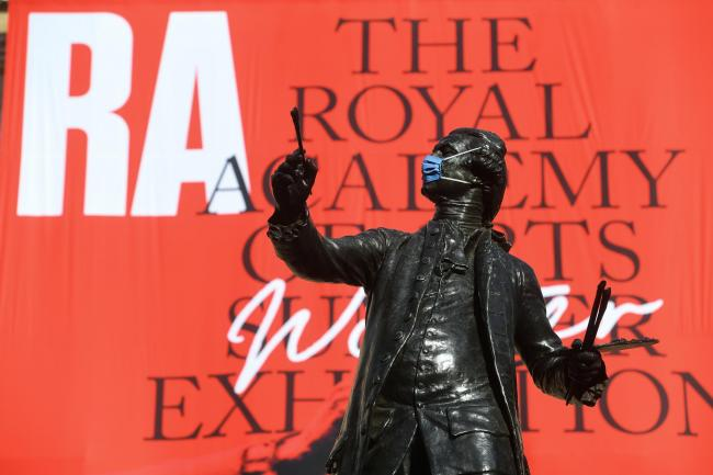The statue of Sir Joshua Reynolds wearing a mask outside the Royal Academy of Arts in London