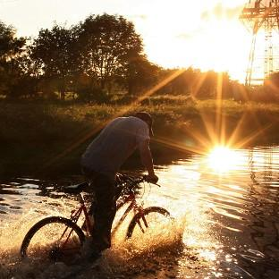 A man cycles through floodwater as torrential downpours cause flash floods in Hebburn (APl)