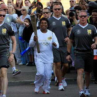 Doreen Lawrence carries the Olympic Flame on the Torch relay leg through Lewisham