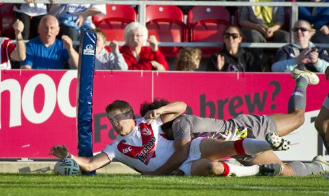 Tommy Makinson touches down for the game's opening try despite the attempt of Luke George to bundle him into touch. Picture by Bernard Platt.