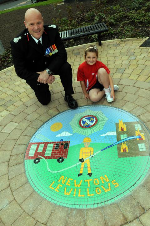 Emilia Lamb, who designed this mosaic for the new station's entrance, with chief fire officer Dan Stephens
