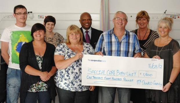 Derek McDonald's family hand over a cheque for £1,800 to Whiston Hospital's special care baby unit.