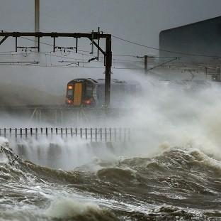 St Helens Star: A train is lashed by waves along the coast at Saltcoats as Scotland has been warned to expect a storm surge.