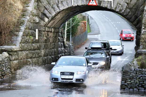 St Helens Star: Drivers negotiate the flooding at Parkside Road