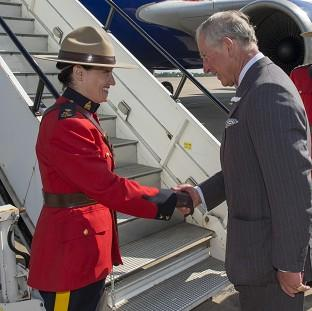 St Helens Star: The Prince of Wales shakes hands with Canadian protection officer, Police Inspector Marie-Claude Cote on departure from RAF Brize Norton in Oxfordshire