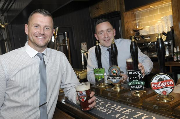 St Helens Star: TOASTING A NEW LOOK: John Glorman and Phil Boal, managers at the Derby Arms, raise a glass after the £200,000 revamp