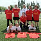 St Helens Star: Members of the Cowley Girls' football team receive their Liverpool FC playing kit for from Nicole Rolser
