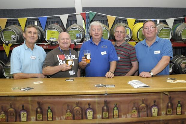 St Helens Star: Age UK Mid Mersey chief executive Mark Lunney (second left) gets ready for the festival rush with bar staff (from left) Dave Roberts, Ray Travies, Keith Hamilton and Russell Owens.