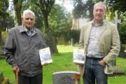 Researchers Richard Waring and Dave Risley with copies of the book, next to the grave of Dave's great grandfather John Henry Sharratt