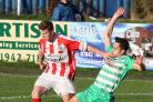 St Helens Town's Declan Gregson rides a tackle from Holker Old Boys