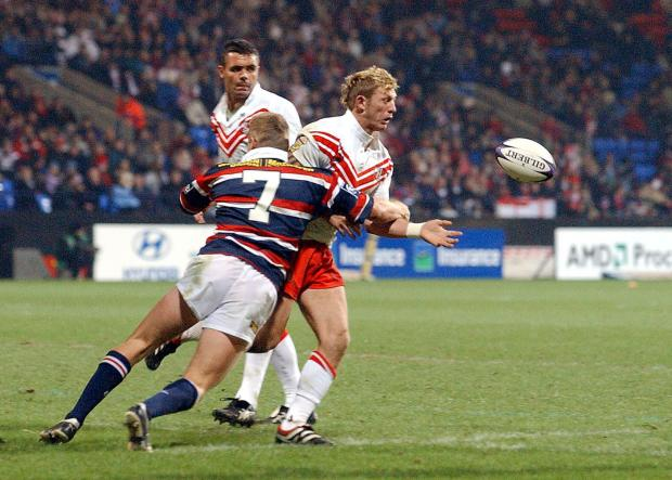 St Helens Star: Sean Long feels the force of a tackle in the World Club Challenge game against Sydney Roosters