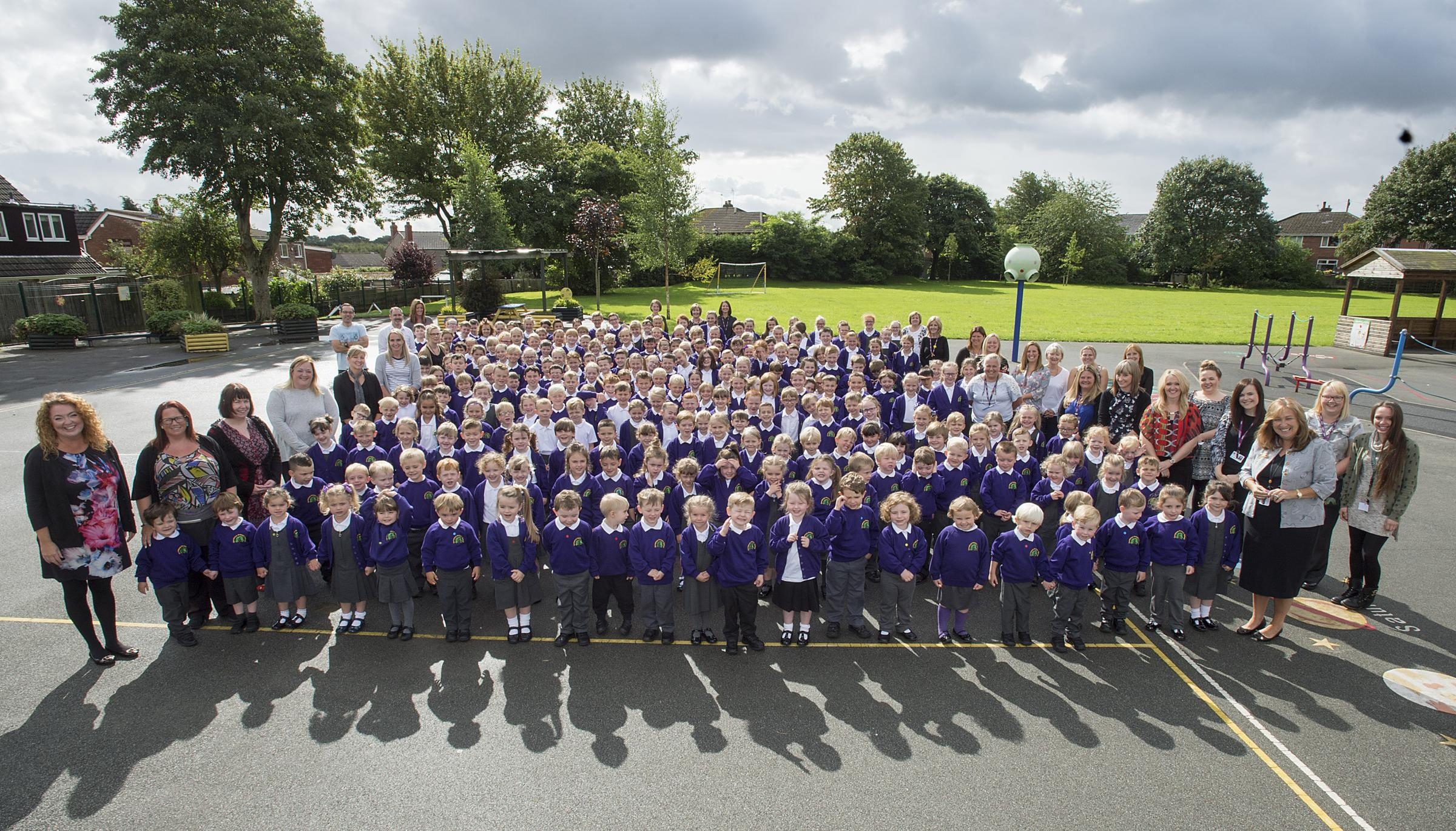 Staff, pupils and Governors at Garswood Primary School celebrate after being judged as outstanding across all areas by Ofsted