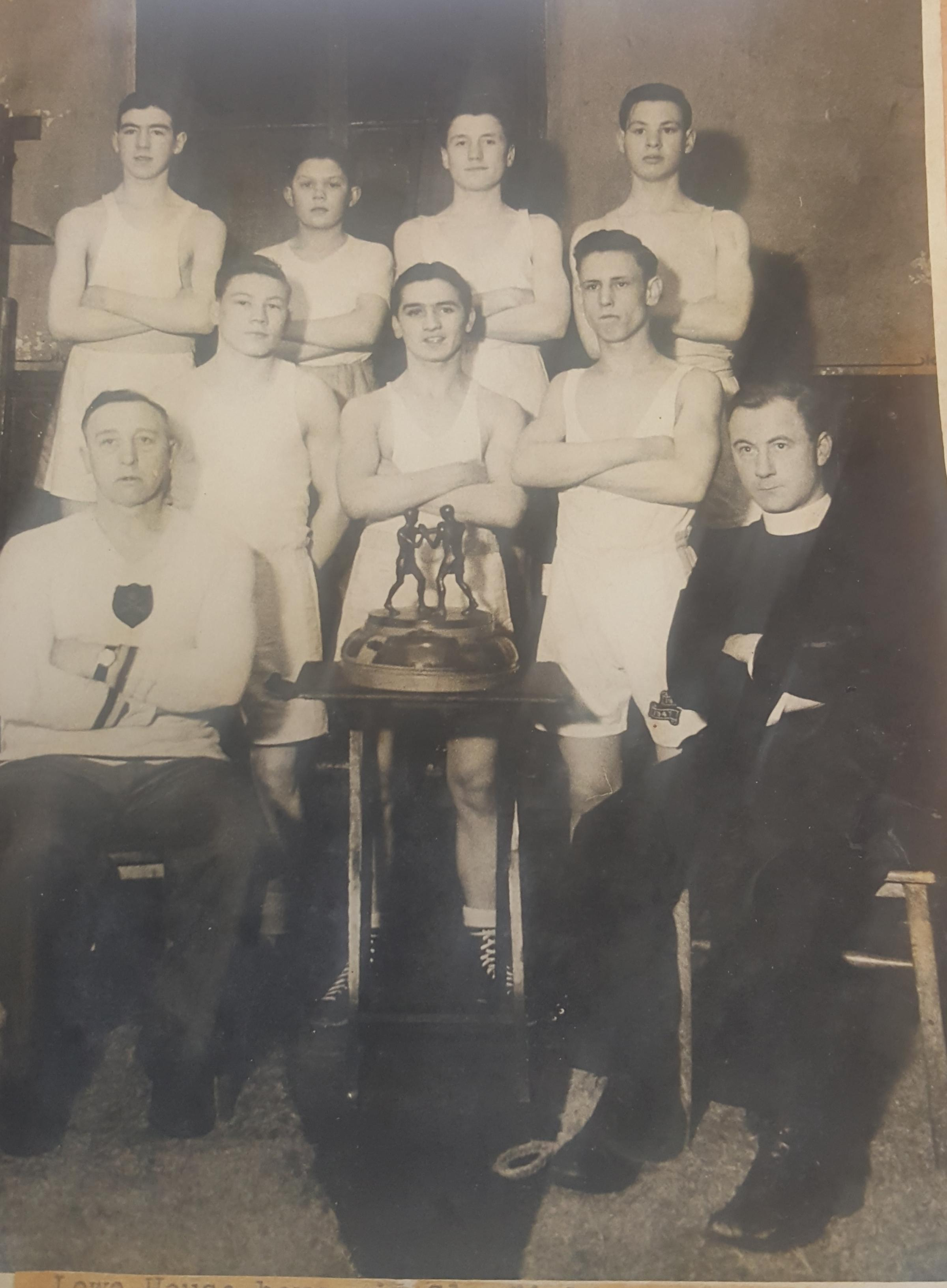 Fighters at Lowe House boxing in the 1940s, with priest Father Kelly and trainer Dick Cowell (front, left) with the International Trophy.Harry Fairclough shared this photograph with the Star. Send your images to news@sthelensstar.co.uk
